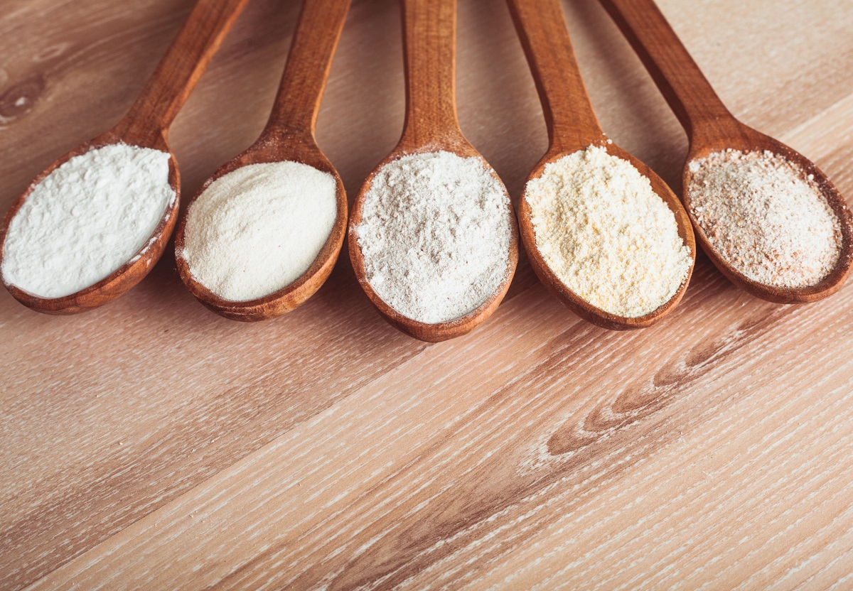25961124 - various types of flour in five wooden spoons